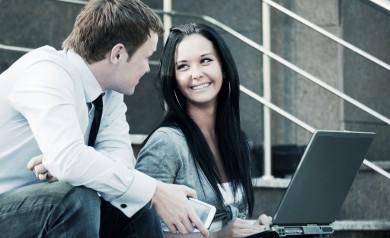 mężczyzna z telefonem dosiada się do dziewczyny z laptopem
